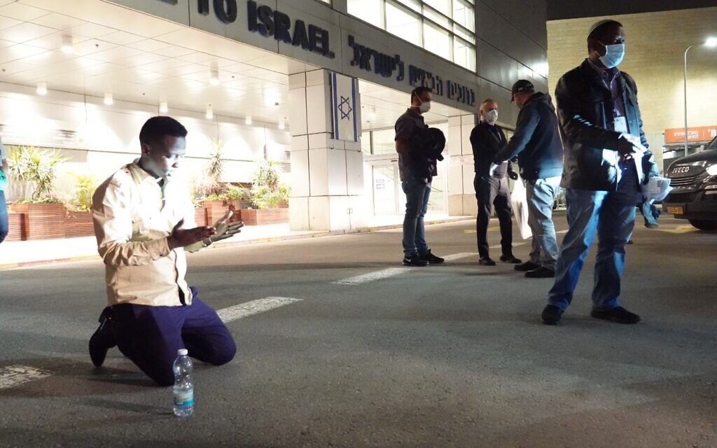 An Ethiopian immigrant kneels on the ground shortly after landing at Ben Gurion Airport, March 24, 2020. (Michael Dimenstein/ GPO)