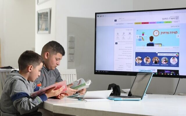 Yongsters learning online at their home in Moshav Yashresh, central Israel, March 18, 2020.  (Yossi Aloni/Flash90)