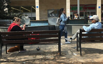 Amid fears of coronavirus, senior citizens in Tel Aviv sit two meters apart on March 15, 2020. (Simona Weinglass/Times of Israel)