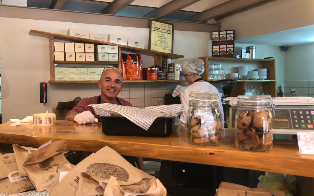 Nissim Naveh mans the counter at the Lechem shel Tomer in Arnona, where customers lined up to buy bread but couldn't sit to drink coffee on March 15, 2020 (Jessica Steinberg/Times of Israel)