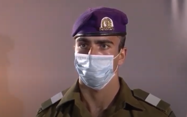 A soldier wearing a protective mask stand at attention  at the national opening ceremony for Israel's Memorial Day for fallen soldeirs and victims of terror, at the Western Wall in Jerusalem, April 27, 2020 (video screenshot)