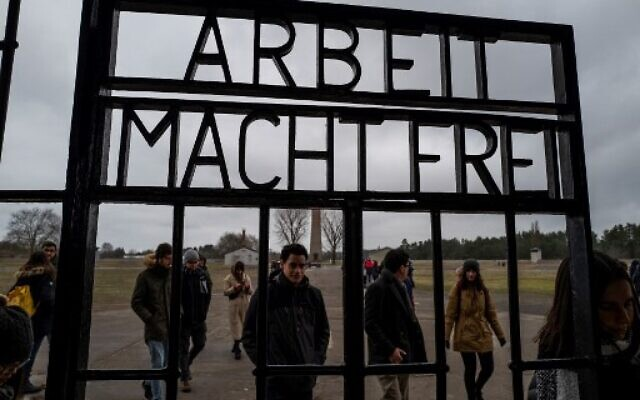 Visitors walk past the gate, inscribed with the words: 'Arbeit Macht Frei' (Work makes you free) of the former Sachsenhausen concentration camp, now a memorial, in Oranienburg, Germany, February 7, 2020. (John MACDOUGALL/AFP)