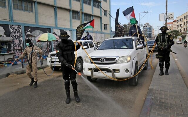 Members of the Palestinian Islamic Jihad terror group's armed wing, the Al-Quds Brigades, spray disinfectant in the streets of Rafah in the southern Gaza Strip on March 26, 2020. (Said Khatib/AFP)