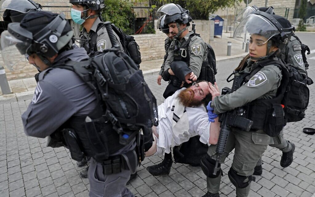 Police arrest an ultra-Orthodox man as they close a synagogue in the Mea Shearim neighborhood in Jerusalem for violating emergency directives to contain the coronavirus, on March 30, 2020. (Ahmad Gharabli/AFP)