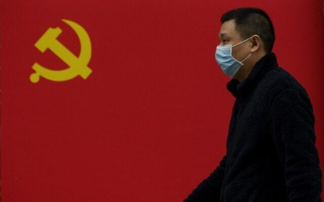A man wearing a face mask as a preventive measure against the coronavirus walks past a Communist Party flag along a street in Wuhan in China's central Hubei province on March 31, 2020. (Noel Celis/AFP)