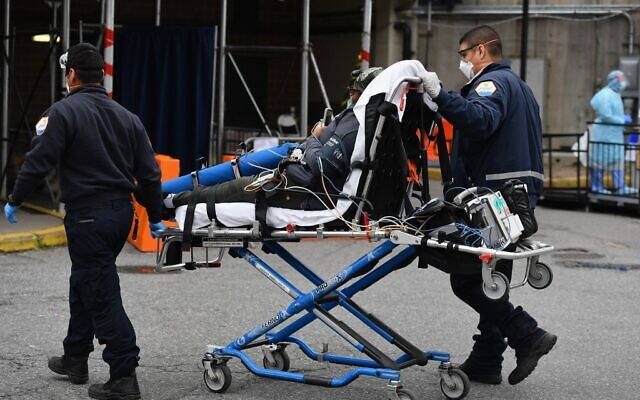 Paramedics push a gurney with a patient to Brooklyn Hospital Center Emergency Room on March 31, 2020 in the Brooklyn borough of New York. (Angela Weiss / AFP)