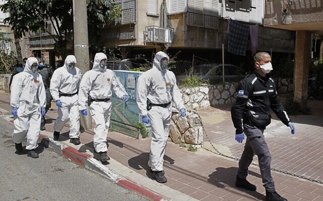 Israeli police officers, dressed in protective outfits, arrive at a yeshiva in the Israeli city of Bnei Brak on April 2, 2020, to ensure that social distancing measures imposed by Israeli authorities meant to curb the spread of the novel coronavirus are being respected. (JACK GUEZ / AFP)