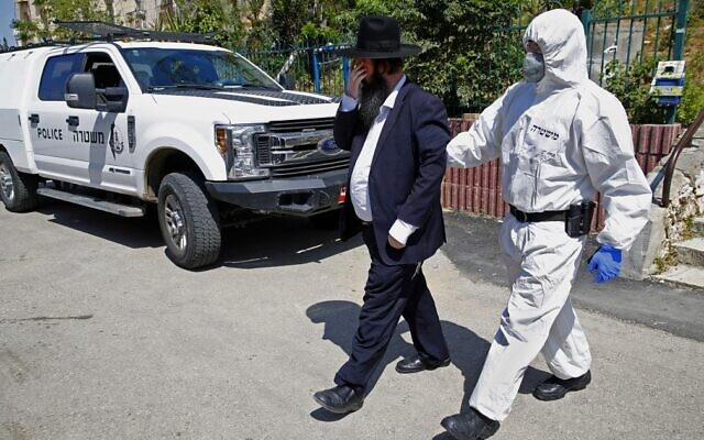 An Israeli police officer in protective gear escorts an ultra-Orthodox man who arrested at a yeshiva in Bnei Brak that was open in violation of emergency directives against the coronavirus, April 2, 2020. (Jack Guez/AFP)