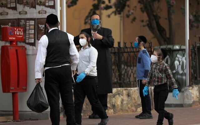Ultra-Orthodox Jewish men and children wearing protective  masks cross gather in a street in the the Ultra-Orthodox Israeli city of Bnei Brak near Tel Aviv on April 2, 2020, during the novel coronavirus pandemic. (MENAHEM KAHANA / AFP)