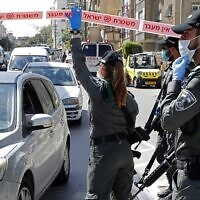 Israeli police officers check vehicles at a checkpoint in the predominantly ultra-Orthodox city of Bnei Brak, near Tel Aviv, on April 3, 2020. (Jack Guez/AFP)