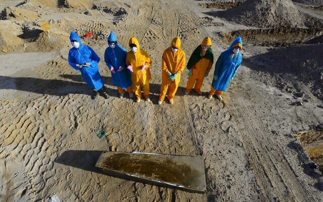 Iraqi volunteers in full hazmat gear pray over the coffin of a fifty-year-old victim of the COVID-19 virus before her burial at a cemetery specifically opened for such deaths, 20 kms from the central holy city of Najaf, on April 3, 2020. (Haidar HAMDANI / AFP)