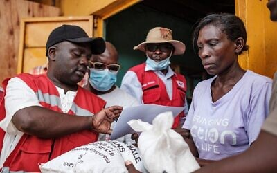Red Cross volunteers register people during the first day of the government's food distribution for people who have been affected by the lockdown in Kampala, Uganda, on April 4, 2020. (SUMY SADURNI/AFP)
