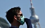 """A protester wears a face mask, during a nationwide action under the motto #LeaveNoOneBehind to protest against Europe external borders and asking to prevent a """"corona catastrophe"""" on April 5, 2020, in front of the landmark TV tower in Berlin, amid the COVID-19 pandemic. (Tobias SCHWARZ / AFP)"""