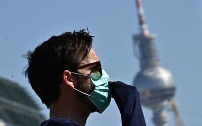 "A protester wears a face mask, during a nationwide action under the motto #LeaveNoOneBehind to protest against Europe external borders and asking to prevent a ""corona catastrophe"" on April 5, 2020, in front of the landmark TV tower in Berlin, amid the COVID-19 pandemic. (Tobias SCHWARZ / AFP)"