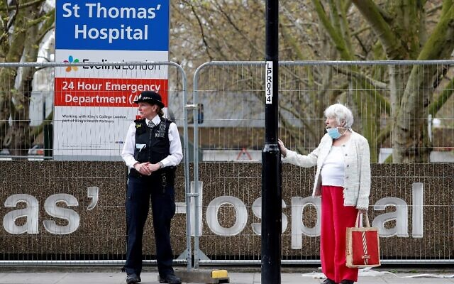 A woman wearing a face mask as a precautionary measure against COVID-19, stands near an on duty police officer outside St Thomas' Hospital in London on April 6, 2020. (Tolga AKMEN / AFP)
