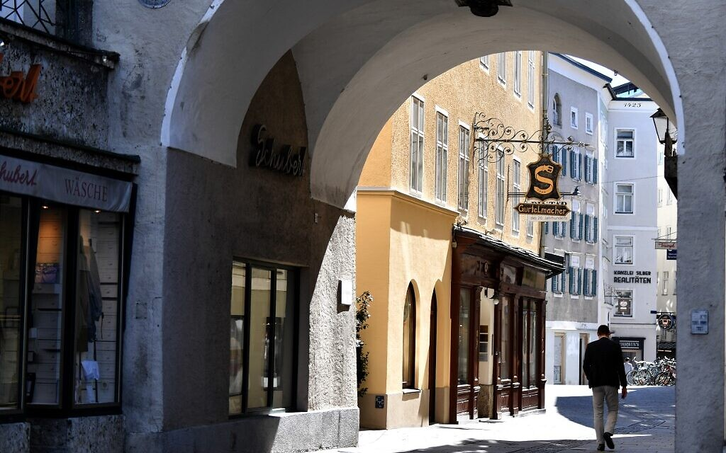 A man walks along an empty street in the old town area of Salzburg on April 6, 2020 during the exit restrictions amid the new coronavirus / Covid-19 pandemic. (BARBARA GINDL / APA / AFP)