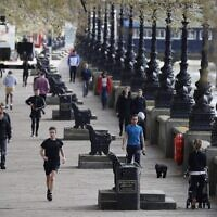 Pedestrians exercise along the embankment in central London as life in Britain continues during the nationwide lockdown to combat the novel coronavirus pandemic on April 6, 2020. (Photo by Tolga AKMEN / AFP)
