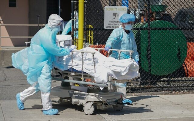 Bodies are moved to a refrigeration truck serving as a temporary morgue at Wyckoff Hospital in the Borough of Brooklyn on April 6, 2020 in New York. (Bryan R. Smith / AFP)