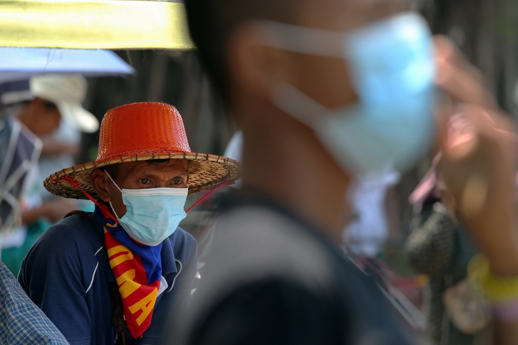 A trishaw driver wearing a face mask amid concerns over the spread of the COVID-19 novel coronavirus waits for food donation in Yangon, Myanmar on April 7, 2020. (Photo by Sai Aung Main / AFP)