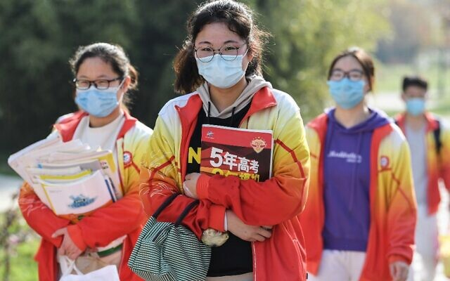 High school grade three students wearing face masks arrive at school after the term opening was delayed due to the COVID-19 coronavirus outbreak, in Bozhou in China's eastern Anhui province on April 7, 2020.(Photo by STR / AFP)