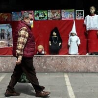 A man walks past a toy shop displaying penitent clothes for children on April 8, 2020, in Seville, Spain, where Easter processions were cancelled during a national lockdown to prevent the spread of the coronavirus disease. (Cristina Quicler/AFP)