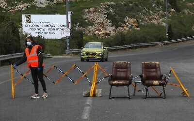 A woman stands next to a makeshift checkpoint in the Druze village of Majdal Shams in the Golan Heights on April 9, 2020. (JALAA MAREY / AFP)