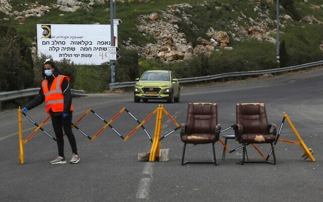 Illustrative: A woman stands next to a makeshift checkpoint in the Druze village of Majdal Shams in the Golan Heights on April 9, 2020. (JALAA MAREY / AFP)