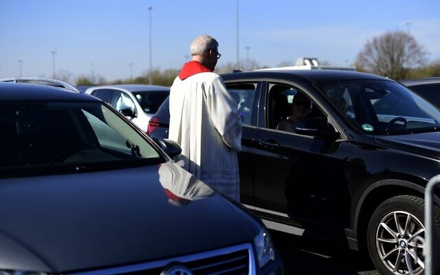 Pastor Frank Heidkamp talks to a visitor in a car during an easter service under the open sky in Duesseldorf drive-in cinema, western Germany, on April 10, 2020, amidst the new coronavirus COVID-19 pandemic. (Ina FASSBENDER / AFP)