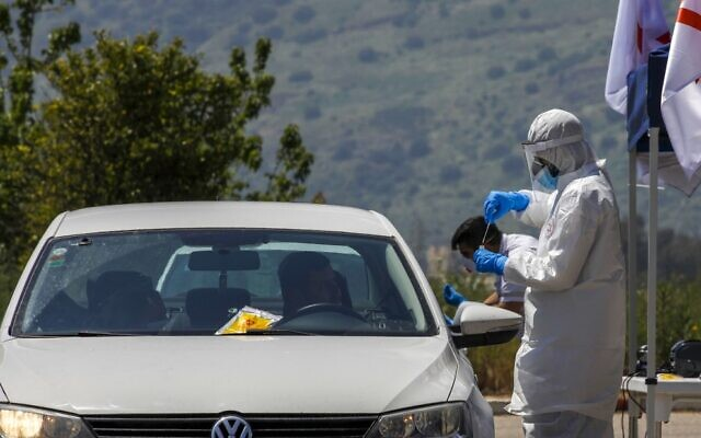 A medical personnel takes a sample from a driver at a Magen David Adom drive-through testing site in the northern city of Kiryat Shmona on April 12, 2020. (Jalaa Marey/AFP)
