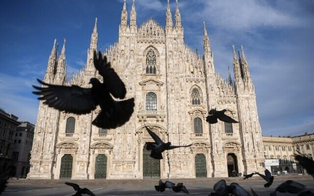 Pigeons fly over a deserted Piazza del Duomo in central Milan on April 12, 2020, during the country's lockdown aimed at curbing the spread of the COVID-19 infection. (Piero CRUCIATTI/AFP)