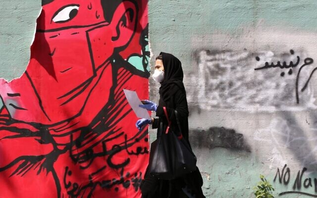 An Iranian woman wearing a protective mask and gloves walks past a mask graffiti in Tehran on April 13, 2020, during the coronavirus COVID-19 pandemic.  (ATTA KENARE / AFP)