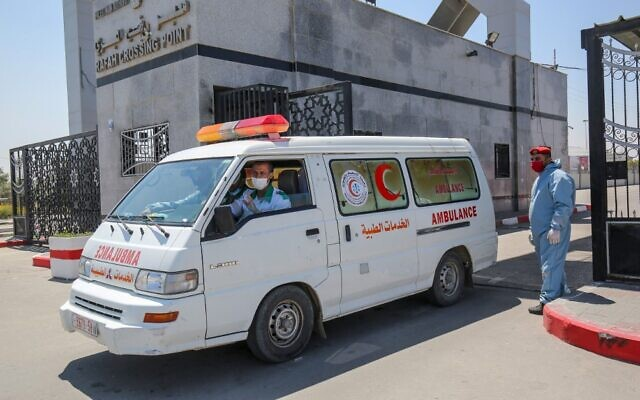 An ambulance drives past a member of security forces loyal to Hamas, the terror group that rules the Gaza Strip, at the Rafah border crossing with Egypt on April 13, 2020. (Said Khatib/AFP)