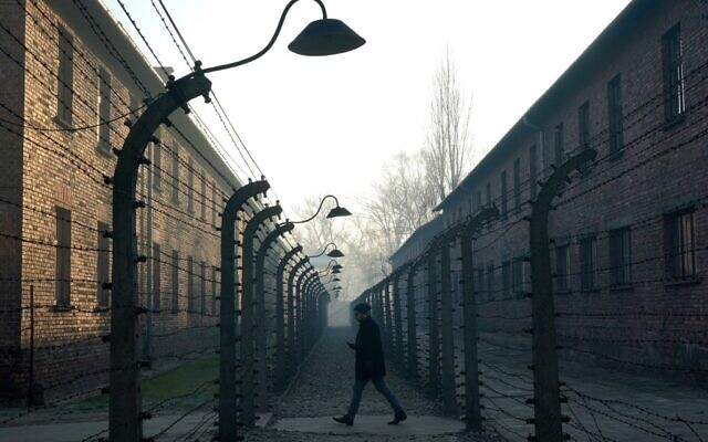 This file photo taken on December 5, 2019 shows a man walking by the barbed wire fence enclosing the memorial site of Auschwitz. (Janek Skarzynski/AFP)