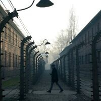 This file photo taken on December 5, 2019 shows a man walking by the barbed wire fence enclosing the memorial site of the former Auschwitz German Nazi death camp. (Janek Skarzynski/AFP)