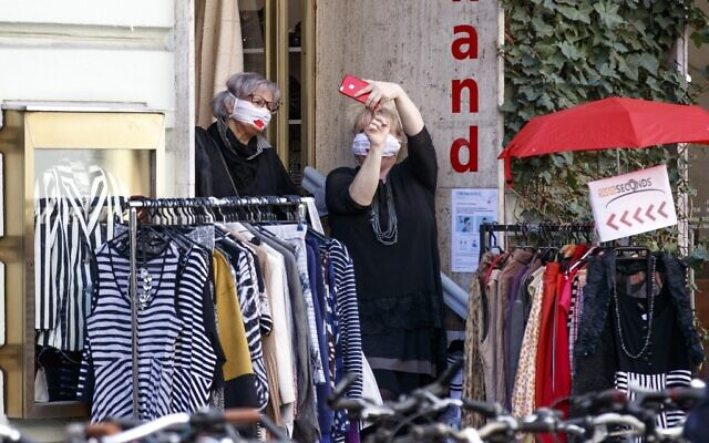 """Women wearing face masks take selfies outside a shop in Graz, Austria, on April 14, 2020 as businesses re-opened following a """"shutdown"""" in a measure to limit the spread of the new coronavirus. (ERWIN SCHERIAU / APA / AFP)"""