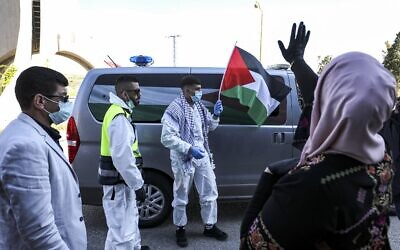 Amir Naji, an 18-year-old Palestinian released by Israel from prison, waves a Palestinian flag while clad in a surgical mask and latex gloves due to the coronavirus pandemic as he is received by his family at a checkpoint near the city of Ramallah in the West Bank on April 14, 2020  (ABBAS MOMANI / AFP)