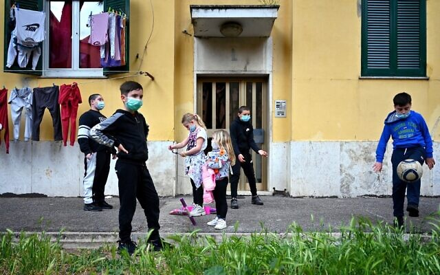 Illustrative: Children wearing protective face masks play football in front of their building in Rome's neighborhood of San Basilio on April 18, 2020, during the country's lockdown aimed at stopping the spread of the novel coronavirus COVID-19. (Alberto PIZZOLI / AFP)