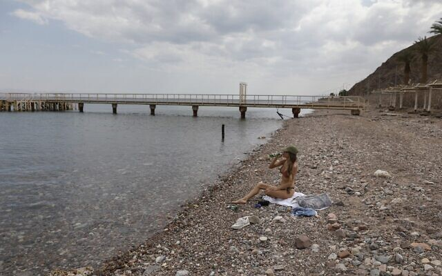 A woman sits along the empty Red Sea shore in the southern resort city of Eilat on April 17, 2020, amid the coronavirus pandemic. (Menahem Kahana/AFP)