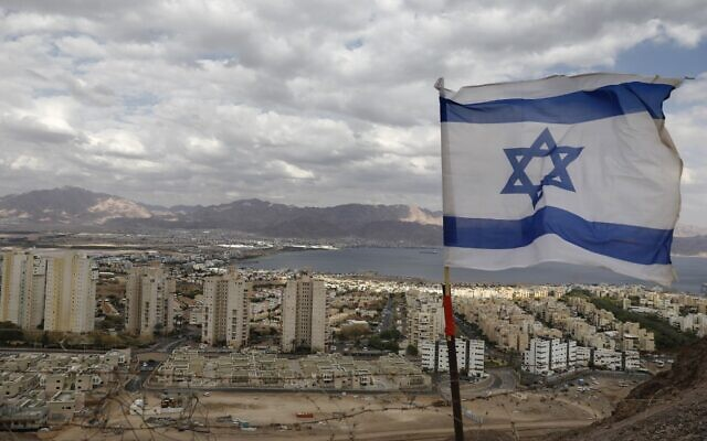 An Israeli flag fluters as the Red Sea resort city of Eilat and Jordan's Red Sea resort city of Aqaba are seen in the background, on April 17, 2020, amid the coronavirus pandemic. (Menahem Kahana/AFP)
