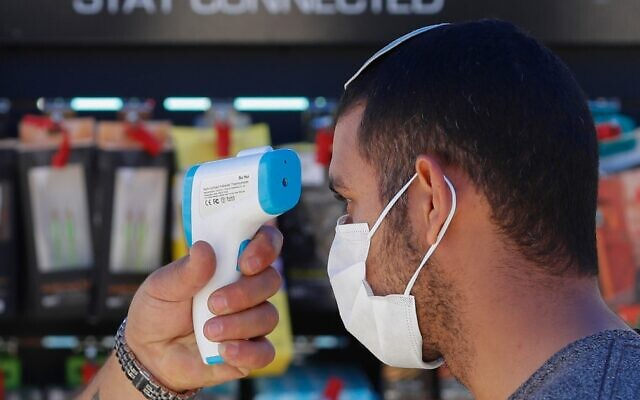 A worker checks the temperature of a customer before allowing him to enter a hardware store in Jerusalem on April 20, 2020, amid the coronavirus pandemic. (Emmanuel Dunand/AFP)