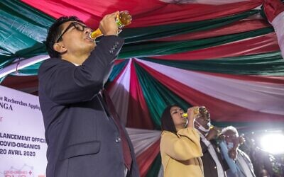 "Madagascar's President Andry Rajoelina drinks a sample of the ""Covid Organics"" or CVO remedy at a launch ceremony in Antananarivo on April 20, 2020. ""Covid Organics"" or CVO is a remedy produced by the Malagasy Institute of Applied Research (IMRA) created from the Artemisia plant and is claimed to help prevent coronavirus Covid-19 infection. (RIJASOLO / AFP)"