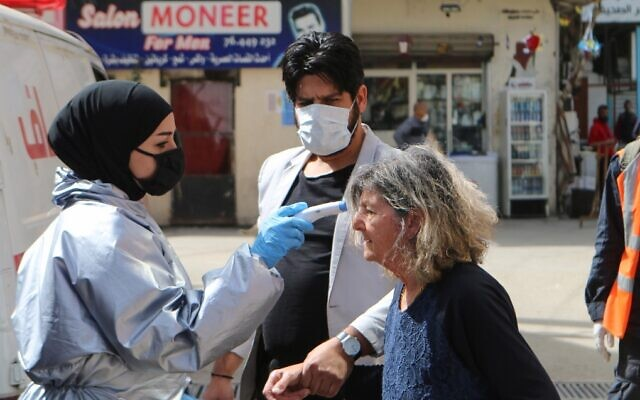 A medic checks the temperature of a woman at the Wavel camp for Palestinian refugees in Lebanon's eastern Bekaa Valley, on April 22, 2020, after the UN announced the first confirmed case of coronavirus there. (AFP)
