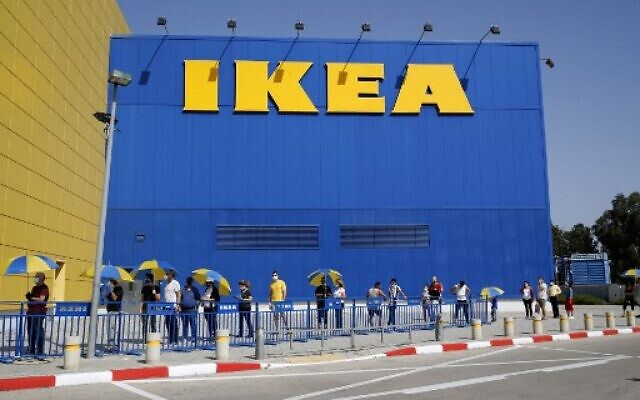 Customers try maintain a safe distance from each other as they wait in line to enter an IKEA outlet in the Israeli coastal town of Netanya on April 22, 2020, after authorities eased down some of the measures that have been in place during the novel conronavirus pandemic crisis. (Photo by JACK GUEZ / AFP)