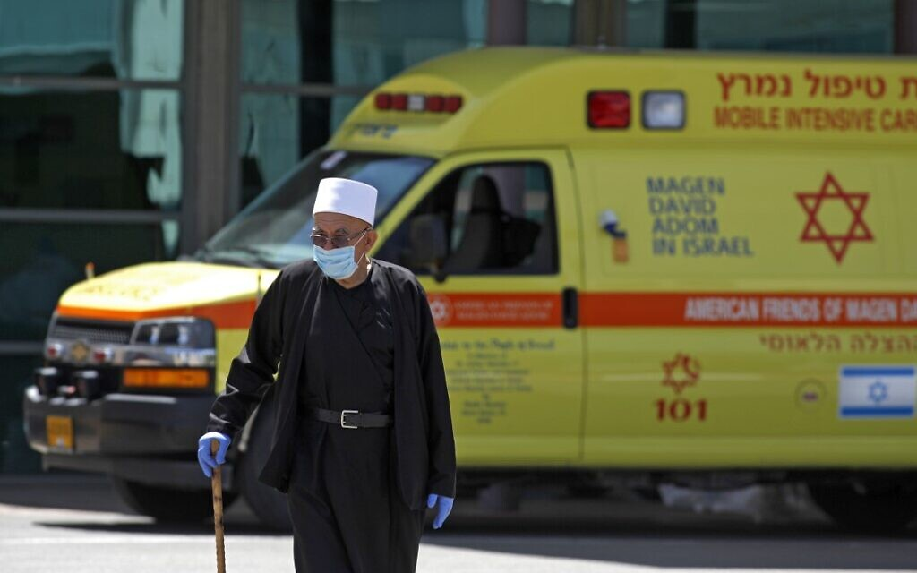 A Druze man wearing a surgical mask walks past an ambulance outside Ziv Medical Center in the northern city of Safed on April 23, 2020. (Jalaa Marey/AFP)