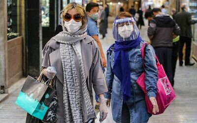 Shoppers clad in protective gear, including face masks and shields and latex gloves, due to the COVID-19 pandemic, walk through the Tajrish Bazaar in Iran's capital Tehran on April 25, 2020, during the Muslim holy month of Ramadan. (ATTA KENARE / AFP)