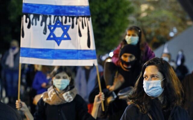 Israelis wearing protective masks and dressed mainly in black take part in a demonstration on April 25, 2020, in Rabin Square in Tel Aviv, to protest what they consider threats to Israeli democracy, against the backdrop of an imminent coalition between Prime Minister Benjamin Netanyahu and his ex-rival Benny Gantz. The protesters stood two meters apart from each other, thereby respecting the social distancing measures in force to fight the COVID-19 pandemic. (JACK GUEZ / AFP)
