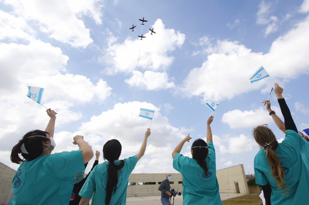 Israeli medical team of Sheba Medical Center at Tel HaShomer wave national flags as Israeli Air Force (IAF) planes fly over the hospital during Israel's Independence day (Yom Ha'atzmaut) celebrations amid the COVID-19 pandemic, in Ramat Gan on April 29, 2020.  (JACK GUEZ / AFP)