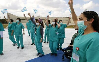 Staff at Sheba Medical Center at Tel HaShomer wave national flags as the Israeli Air Force aerobatic team fly over the hospital during Israel's Independence day celebrations in a salute to medical teams fighting the coronavirus outbreak, April 29, 2020. (JACK GUEZ/AFP)