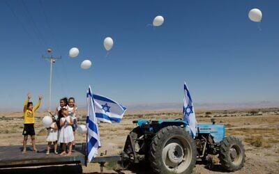 Israeli children realease white balloons during a small ceremony held near their agricultural enclave, at the crossing checkpoint near Moshav Tzofar, on the Israeli-Jordanian border on April 30, 2020. (MENAHEM KAHANA / AFP)