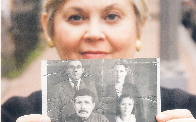 Esther Safran Foer holds a black and white photo of her father, Louis, top left, and the family that hid him during the war. (Courtesy)